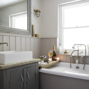 Inspiration for a medium sized country family bathroom in Cornwall with shaker cabinets, grey cabinets, a built-in bath, a shower/bath combination, a one-piece toilet, white tiles, white walls, painted wood flooring, a trough sink and white floors.