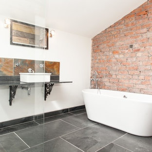 Inspiration for a mid-sized industrial bathroom in Other with a freestanding tub, a one-piece toilet, black tile, white walls, slate floors, a vessel sink, an open shower and slate.