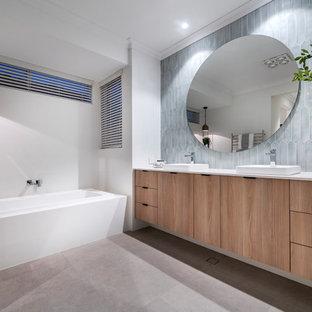 Foto de cuarto de baño principal, actual, con armarios con paneles lisos, puertas de armario de madera oscura, bañera encastrada, baldosas y/o azulejos grises, paredes blancas, lavabo encastrado, suelo gris y encimeras blancas