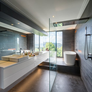 Photo of a modern master bathroom in Cairns with flat-panel cabinets, white cabinets, a freestanding tub, an open shower, black tile, black walls, a vessel sink and black floor.