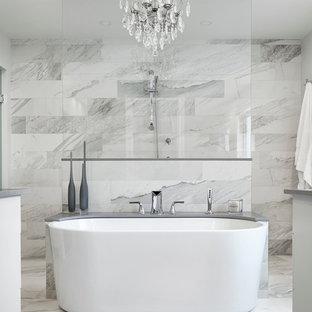 Inredning av ett klassiskt en-suite badrum, med ett fristående badkar, en kantlös dusch, grå kakel, vit kakel, marmorgolv, släta luckor, vita skåp, marmorkakel och med dusch som är öppen