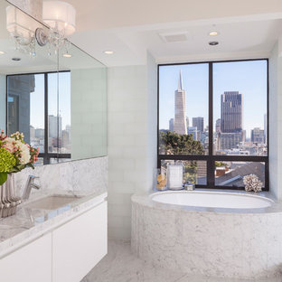 Inspiration for a contemporary master white tile and glass tile bathroom remodel in San Francisco with flat-panel cabinets, white cabinets, an undermount tub and an undermount sink