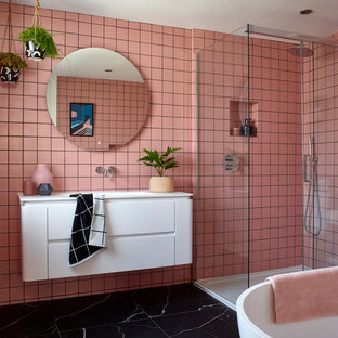 Inspiration for a contemporary bathroom in London with flat-panel cabinets, white cabinets, a freestanding bath, a corner shower, pink tiles, pink walls, an integrated sink, black floors, a sliding door and white worktops.