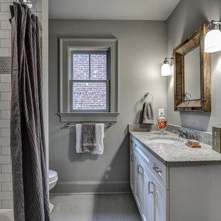 Inredning av ett klassiskt litet badrum, med ett undermonterad handfat, skåp i shakerstil, vita skåp, granitbänkskiva, grå kakel, keramikplattor, grå väggar och klinkergolv i keramik