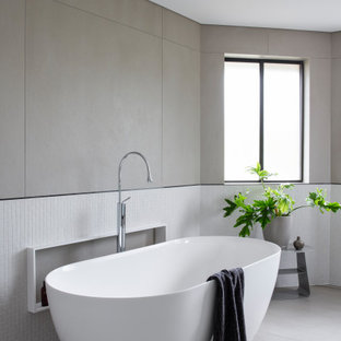 This is an example of a large contemporary bathroom in Sydney with a freestanding tub, multi-coloured tile, mosaic tile, porcelain floors and grey floor.