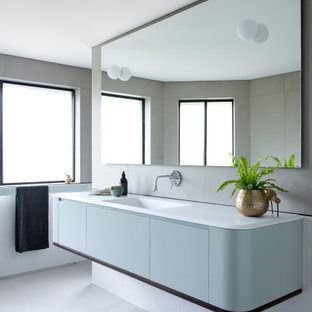 Large contemporary bathroom in Sydney with blue cabinets, mosaic tile, porcelain floors, an integrated sink, solid surface benchtops, grey floor, white benchtops, flat-panel cabinets and white tile.