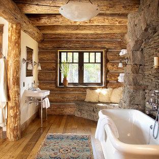 Bild på ett rustikt badrum, med ett konsol handfat och ett fristående badkar