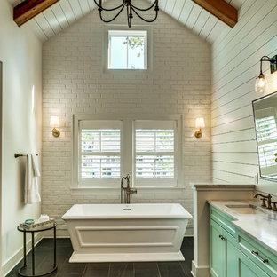 Diseño de cuarto de baño principal, de estilo de casa de campo, extra grande, con armarios estilo shaker, puertas de armario turquesas, bañera exenta, paredes blancas, suelo de baldosas de cerámica, lavabo bajoencimera y suelo gris