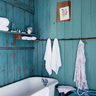 This is an example of a shabby-chic style bathroom in Los Angeles with a claw-foot tub and blue walls.