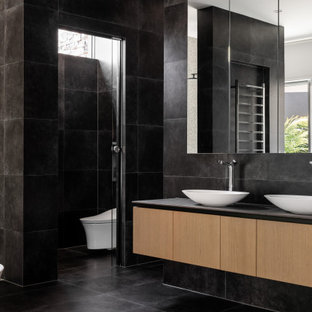 Design ideas for a contemporary master bathroom in Perth with flat-panel cabinets, medium wood cabinets, a freestanding tub, a wall-mount toilet, black tile, white walls, a vessel sink, black floor, grey benchtops, an enclosed toilet, a double vanity and a floating vanity.