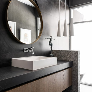 Contemporary bathroom in Perth with flat-panel cabinets, medium wood cabinets, black tile, a vessel sink, black floor and black benchtops.