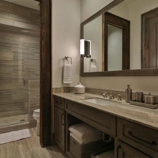 Inspiration för ett stort funkis en-suite badrum, med luckor med infälld panel, skåp i mörkt trä, en dubbeldusch, en toalettstol med hel cisternkåpa, beige kakel, stenhäll, beige väggar, kalkstensgolv, ett undermonterad handfat och bänkskiva i kalksten