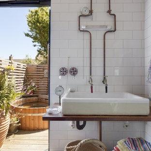 Photo of a beach style bathroom in Kent with white tiles, metro tiles, white walls, medium hardwood flooring, a vessel sink, wooden worktops, brown floors and brown worktops.