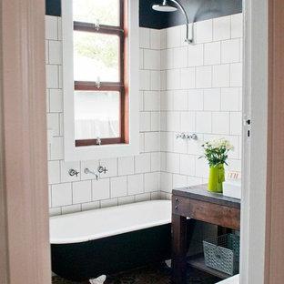 Immagine di una stanza da bagno vittoriana con vasca con piedi a zampa di leone, piastrelle bianche, pareti nere, pavimento in cemento, lavabo a bacinella, consolle stile comò, ante in legno bruno, vasca/doccia e pavimento multicolore