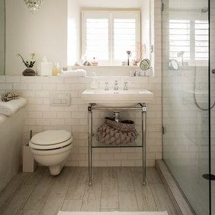 Modelo de cuarto de baño infantil, contemporáneo, de tamaño medio, con ducha a ras de suelo, sanitario de pared, baldosas y/o azulejos blancos, baldosas y/o azulejos de cerámica, paredes blancas, suelo de madera clara, lavabo suspendido y suelo beige