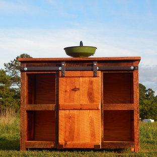 Diseño de cuarto de baño de estilo de casa de campo, de tamaño medio, con lavabo sobreencimera, armarios abiertos, puertas de armario de madera oscura y encimera de madera