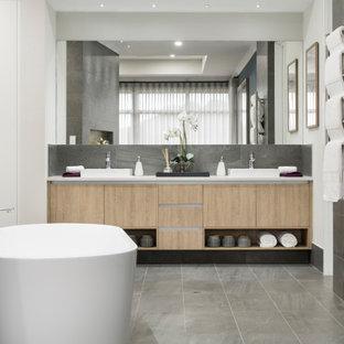 Idéer för att renovera ett mellanstort funkis vit vitt en-suite badrum, med släta luckor, skåp i ljust trä, en dusch i en alkov, grå kakel, porslinskakel, vita väggar, ett fristående handfat, grått golv och dusch med gångjärnsdörr