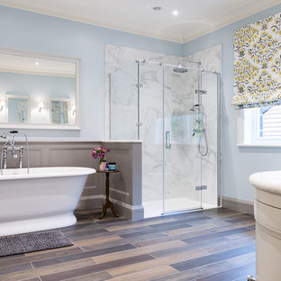 Photo of a large traditional ensuite bathroom in Other with recessed-panel cabinets, white cabinets, a freestanding bath, a built-in shower, a one-piece toilet, blue tiles, blue walls, porcelain flooring, a built-in sink, marble worktops, brown floors, a hinged door and white worktops.