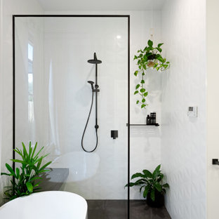 Design ideas for a mid-sized contemporary bathroom in Melbourne with a freestanding tub, ceramic floors, an open shower, a curbless shower, white tile, white walls and grey floor.