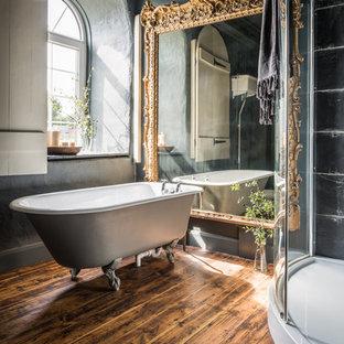 Modelo de cuarto de baño principal, clásico, grande, con bañera con patas, baldosas y/o azulejos negros, paredes grises, suelo de madera oscura y ducha esquinera