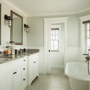 Example of a large coastal master gray tile and porcelain tile ceramic floor freestanding bathtub design in Portland Maine with an undermount sink, recessed-panel cabinets, white cabinets, engineered quartz countertops and gray countertops