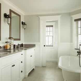Cette image montre une grande salle de bain principale marine avec un lavabo encastré, un placard avec porte à panneau encastré, des portes de placard blanches, un plan de toilette en quartz modifié, une baignoire indépendante, un carrelage gris, des carreaux de porcelaine, un sol en carrelage de céramique et un plan de toilette gris.