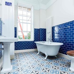 Imagen de cuarto de baño clásico, de tamaño medio, con bañera con patas, baldosas y/o azulejos azules, baldosas y/o azulejos de cemento, paredes marrones, suelo azul, sanitario de una pieza, suelo de baldosas de cerámica y lavabo tipo consola