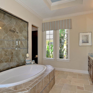 Design ideas for a mediterranean ensuite bathroom in Tampa with raised-panel cabinets, dark wood cabinets, a built-in bath, a double shower, a two-piece toilet, beige tiles, ceramic tiles, beige walls, travertine flooring, a submerged sink and granite worktops.