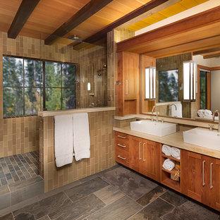 Modelo de cuarto de baño principal, rural, grande, con lavabo sobreencimera, armarios estilo shaker, puertas de armario de madera oscura, encimera de piedra caliza, ducha empotrada, baldosas y/o azulejos de cerámica, paredes blancas, suelo de pizarra y baldosas y/o azulejos marrones