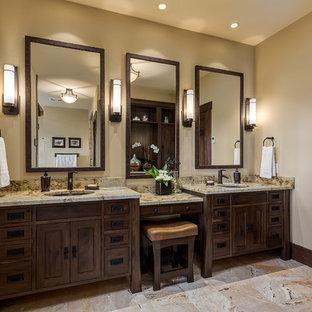 カルガリーの広いおしゃれなマスターバスルーム (アンダーカウンター洗面器、濃色木目調キャビネット、御影石の洗面台、ベージュのタイル、石タイル、黄色い壁、トラバーチンの床、家具調キャビネット) の写真