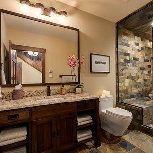 Diseño de cuarto de baño con ducha, de estilo americano, grande, con lavabo bajoencimera, puertas de armario de madera en tonos medios, encimera de granito, sanitario de una pieza, baldosas y/o azulejos marrones, paredes amarillas, suelo de pizarra, armarios tipo mueble, ducha empotrada y baldosas y/o azulejos de pizarra