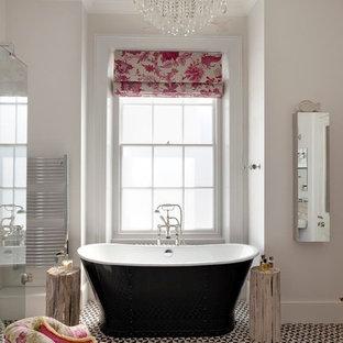 Klassisk inredning av ett en-suite badrum, med ett fristående badkar och grå väggar