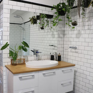 Photo of an industrial master bathroom in Brisbane with an open shower, subway tile, white walls, mosaic tile floors, wood benchtops, black floor, an open shower, flat-panel cabinets, white cabinets, brown benchtops, white tile and a drop-in sink.