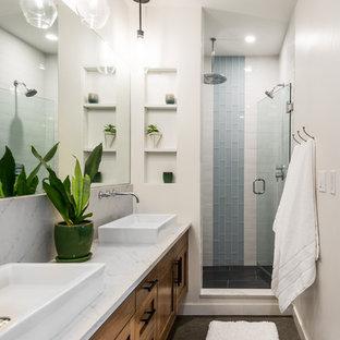 Выдающиеся фото от архитекторов и дизайнеров интерьера: ванная комната среднего размера в современном стиле с фасадами в стиле шейкер, душем в нише, белой плиткой, керамической плиткой, белыми стенами, бетонным полом, душевой кабиной, настольной раковиной, столешницей из искусственного кварца, душем с распашными дверями, белой столешницей, темными деревянными фасадами и серым полом