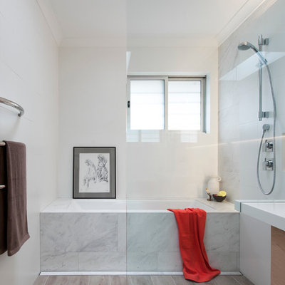 Inspiration for a small contemporary 3/4 white tile and ceramic tile ceramic tile bathroom remodel in Sydney with a wall-mount sink, light wood cabinets, solid surface countertops, an undermount tub, white walls and flat-panel cabinets