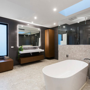 Contemporary master bathroom in Melbourne with flat-panel cabinets, dark wood cabinets, a freestanding tub, a double shower, black tile, gray tile, black walls, grey floor and white benchtops.