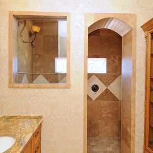 Modelo de cuarto de baño infantil, mediterráneo, de tamaño medio, con armarios con paneles con relieve, puertas de armario de madera en tonos medios, ducha empotrada, sanitario de dos piezas, baldosas y/o azulejos marrones, baldosas y/o azulejos de terracota, paredes amarillas, suelo de travertino, lavabo bajoencimera y encimera de granito