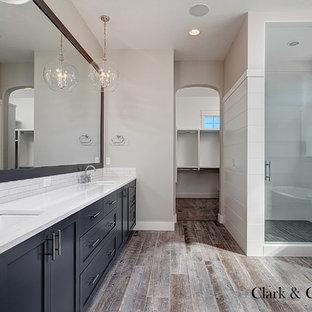 Imagen de cuarto de baño principal, campestre, grande, con lavabo bajoencimera, armarios con paneles empotrados, puertas de armario grises, encimera de cuarzo compacto, bañera exenta, ducha abierta, baldosas y/o azulejos blancos, baldosas y/o azulejos de cemento, paredes grises y suelo de baldosas de porcelana
