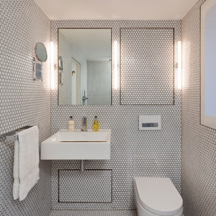 Trendy white tile and mosaic tile mosaic tile floor bathroom photo in London with a one-piece toilet, a wall-mount sink and white walls