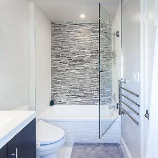 ワシントンD.C.の小さいモダンスタイルのおしゃれなマスターバスルーム (一体型シンク、フラットパネル扉のキャビネット、濃色木目調キャビネット、人工大理石カウンター、ドロップイン型浴槽、アルコーブ型シャワー、ビデ、白いタイル、セラミックタイル、グレーの壁、大理石の床) の写真