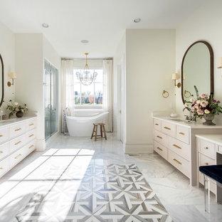 インディアナポリスの大きいトランジショナルスタイルのおしゃれなマスターバスルーム (レイズドパネル扉のキャビネット、ベージュのキャビネット、置き型浴槽、洗い場付きシャワー、分離型トイレ、白いタイル、セラミックタイル、白い壁、大理石の床、オーバーカウンターシンク、珪岩の洗面台、白い床、開き戸のシャワー) の写真