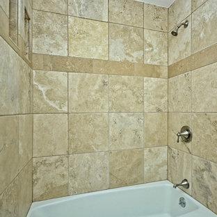 Idee per una piccola stanza da bagno padronale american style con ante lisce, ante bianche, vasca da incasso, vasca/doccia, piastrelle beige, piastrelle in pietra, pareti grigie, pavimento in pietra calcarea, lavabo da incasso e top in pietra calcarea