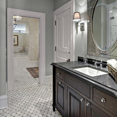 Bathroom - traditional bathroom idea in Minneapolis with raised-panel cabinets, dark wood cabinets, gray walls, an undermount sink and granite countertops