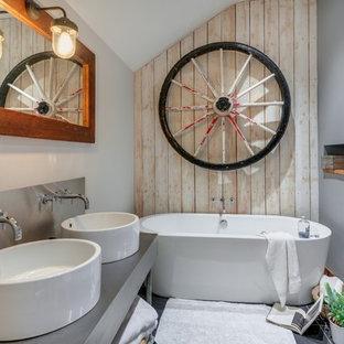 Ejemplo de cuarto de baño principal, rural, de tamaño medio, con armarios tipo mueble, bañera exenta, sanitario de pared, baldosas y/o azulejos grises, paredes grises, suelo de pizarra, lavabo de seno grande, encimera de acero inoxidable y suelo gris