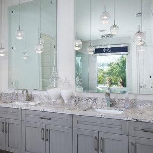 Immagine di una stanza da bagno padronale costiera con ante in stile shaker, ante grigie, vasca giapponese, doccia a filo pavimento, piastrelle rosa, pareti bianche, pavimento in gres porcellanato, lavabo sottopiano e top in laminato