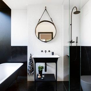 Ejemplo de cuarto de baño principal, actual, pequeño, con bañera exenta, ducha abierta, sanitario de pared, baldosas y/o azulejos blancos, baldosas y/o azulejos de mármol, paredes blancas, suelo de mármol, suelo negro, ducha abierta y lavabo tipo consola