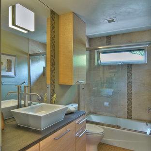 Idee per una piccola stanza da bagno tradizionale con lavabo a bacinella, ante lisce, ante in legno chiaro, vasca ad alcova, vasca/doccia, WC a due pezzi, piastrelle multicolore, piastrelle di vetro, pareti grigie e pavimento in sughero