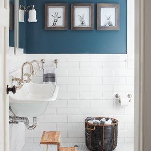 Inredning av ett lantligt badrum, med blå väggar, mosaikgolv och ett avlångt handfat