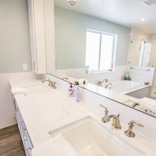 マイアミの大きいビーチスタイルのおしゃれなマスターバスルーム (シェーカースタイル扉のキャビネット、白いキャビネット、ドロップイン型浴槽、アルコーブ型シャワー、グレーの壁、濃色無垢フローリング、アンダーカウンター洗面器、珪岩の洗面台、茶色い床、開き戸のシャワー、白い洗面カウンター) の写真