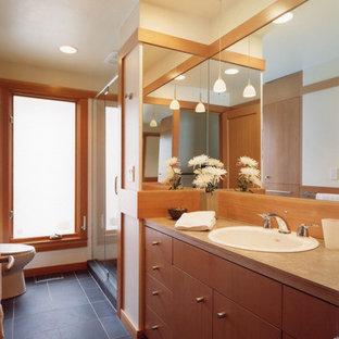 Ispirazione per una stanza da bagno con doccia tradizionale di medie dimensioni con lavabo da incasso, ante lisce, ante in legno scuro, top in laminato, doccia alcova, WC a due pezzi, piastrelle nere, piastrelle in pietra, pareti beige e pavimento in ardesia